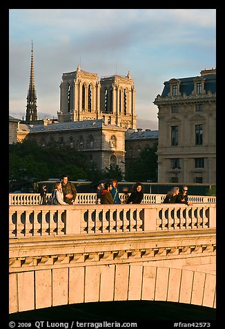 Watching the sunset from a bridge, with Notre Dame towers behind. Paris, France (color)