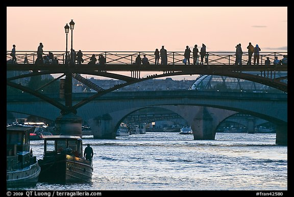 Seine river and people silhouettes on Pont des Arts. Paris, France