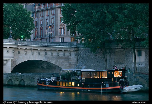 Lighted live-in barge, quay, and Pont-Neuf. Paris, France