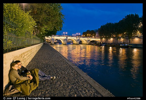 Couple sitting on quay on banks of the Seine River. Paris, France (color)