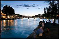People sitting on tip of Ile de la Cite at sunset. Paris, France