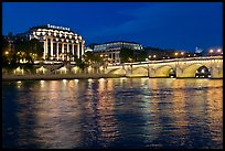 Pont Neuf and Samaritaine reflected in Seine River at night. Paris, France (color)