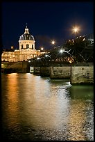 Institut de France and Pont des Arts reflected in Seine river at night. Paris, France