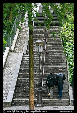 Couple walking up steet stairs, Montmartre. Paris, France (color)