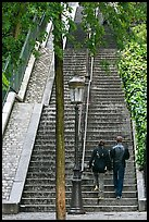 Couple walking up steet stairs, Montmartre. Paris, France