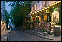 Cobblestone street and restaurant at dusk, Montmartre. Paris, France