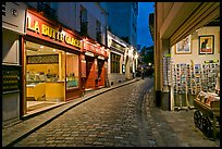 Narrow cobblestone street and businesses at night, Montmartre. Paris, France ( color)