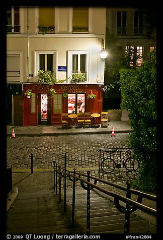 Hillside stairs on butte, street and restaurant at night, Montmartre. Paris, France (color)