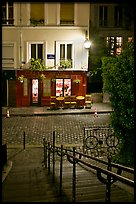 Hillside stairs on butte, street and restaurant at night, Montmartre. Paris, France ( color)