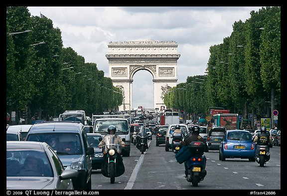 Car and motorcycle traffic and Arc de Triomphe, Champs-Elysees. Paris, France