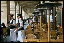 Waiters and cafe in place Victor Hugo arcades. Paris, France