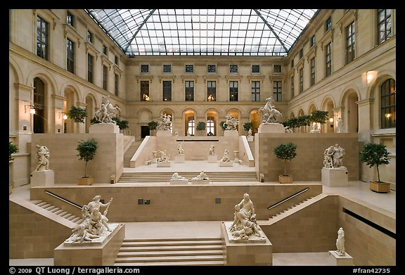 Louvre Museum room with sculptures and skylight. Paris, France