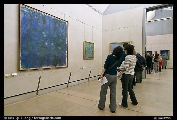 Visitors looking at a large impressionist painting of a lilly pond. Paris, France