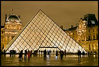 People standing in front of Louvre Pyramid by night. Paris, France