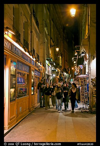 People walking in pedestrian street at night. Quartier Latin, Paris, France (color)