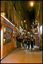 People walking in pedestrian street at night. Quartier Latin, Paris, France
