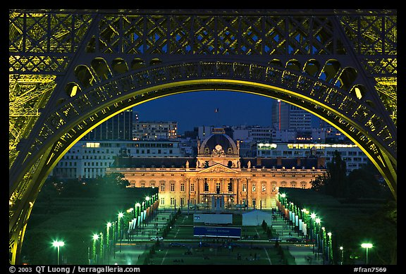 Ecole Militaire (Military Academy) seen through Eiffel Tower at night. Paris, France