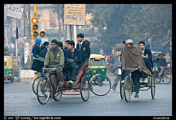 Cycle-rickshaws carrying uniformed schoolchildren. New Delhi, India (color)