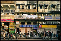 Street with many people waiting in front of closed stores, Old Delhi. New Delhi, India ( color)