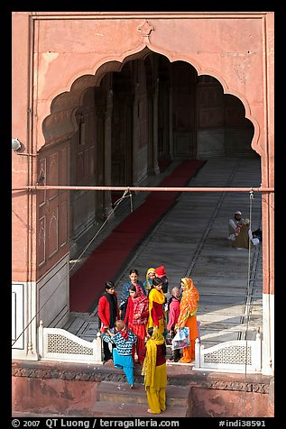 Women standing beneath arched entrance of prayer hall, Jama Masjid. New Delhi, India (color)