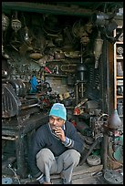 Man sitting in front of machine parts shop, Old Delhi. New Delhi, India