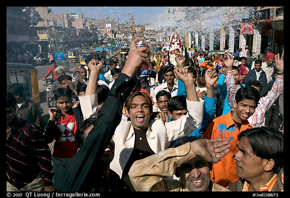 Young men celebrating and spraying wedding party in the street. Jodhpur, Rajasthan, India