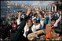Young men celebrating and spraying wedding party in the street. Jodhpur, Rajasthan, India (color)