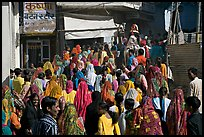 Street with women in colorful sari following wedding procession. Jodhpur, Rajasthan, India (color)