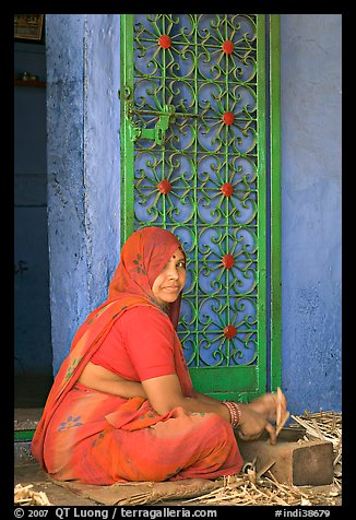 Woman in orange sari sitting next to green door and blue wall. Jodhpur, Rajasthan, India