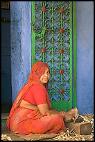 Woman in orange sari sitting next to green door and blue wall. Jodhpur, Rajasthan, India (color)