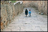 Children walking on the stone ramp leading to the fort. Jodhpur, Rajasthan, India