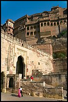 Couple walking below gate and high walls, Mehrangarh Fort. Jodhpur, Rajasthan, India ( color)