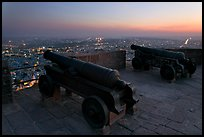 Cannons on top of Mehrangarh Fort, and city lights and dusk. Jodhpur, Rajasthan, India (color)