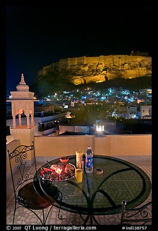 Rooftop restaurant table with food served and view of Mehrangarh Fort by night. Jodhpur, Rajasthan, India