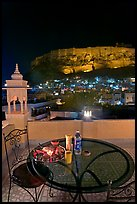Rooftop restaurant table with food served and view of Mehrangarh Fort by night. Jodhpur, Rajasthan, India (color)