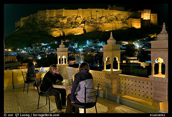 Travelers on rooftop terrace with view of Mehrangarh Fort by night. Jodhpur, Rajasthan, India