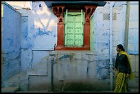 Woman walks infront of blue tinted whitewashed wall. Jodhpur, Rajasthan, India