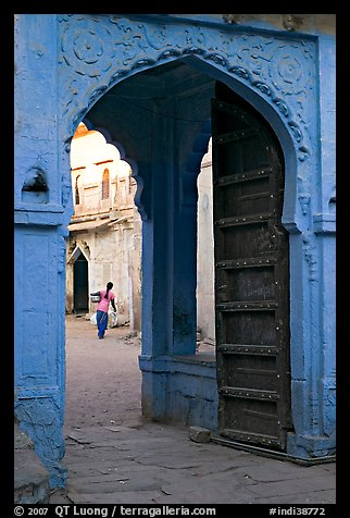 Archway with woman carrying water in courtyard. Jodhpur, Rajasthan, India
