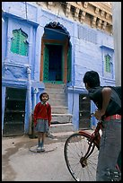 Boy on bicycle looking at girl in front of blue house. Jodhpur, Rajasthan, India
