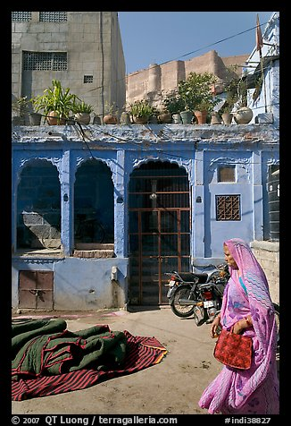 Woman in sari, blue house, and fort in the distance. Jodhpur, Rajasthan, India (color)