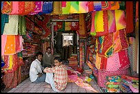 Men in shop selling colorful fabrics, Sardar market. Jodhpur, Rajasthan, India (color)