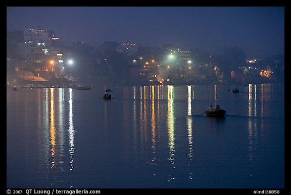 Rowboats and reflected lights on the Ganges River at dusk. Varanasi, Uttar Pradesh, India