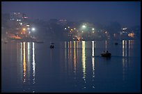 Rowboats and reflected lights on the Ganges River at dusk. Varanasi, Uttar Pradesh, India (color)