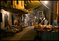 Flower vendor in  narrow old city alley at night. Varanasi, Uttar Pradesh, India (color)