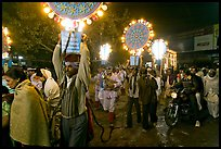 Men carrying bright electric signs during wedding procession. Varanasi, Uttar Pradesh, India