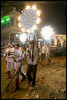 Uniformed musicians and men carrying lights during wedding procession. Varanasi, Uttar Pradesh, India (color)