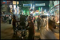 Men pulling generator on bicycle to power lights during wedding procession. Varanasi, Uttar Pradesh, India (color)