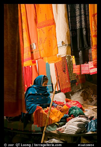 Woman selling fabrics at night. Varanasi, Uttar Pradesh, India (color)