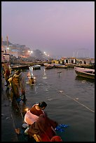 Women soaking clothes in the Ganges River at dawn. Varanasi, Uttar Pradesh, India
