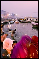 Women on the banks of the Ganga River in rosy dawn light. Varanasi, Uttar Pradesh, India (color)
